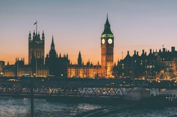A photograph of the Houses of Parliament shortly after sunset.