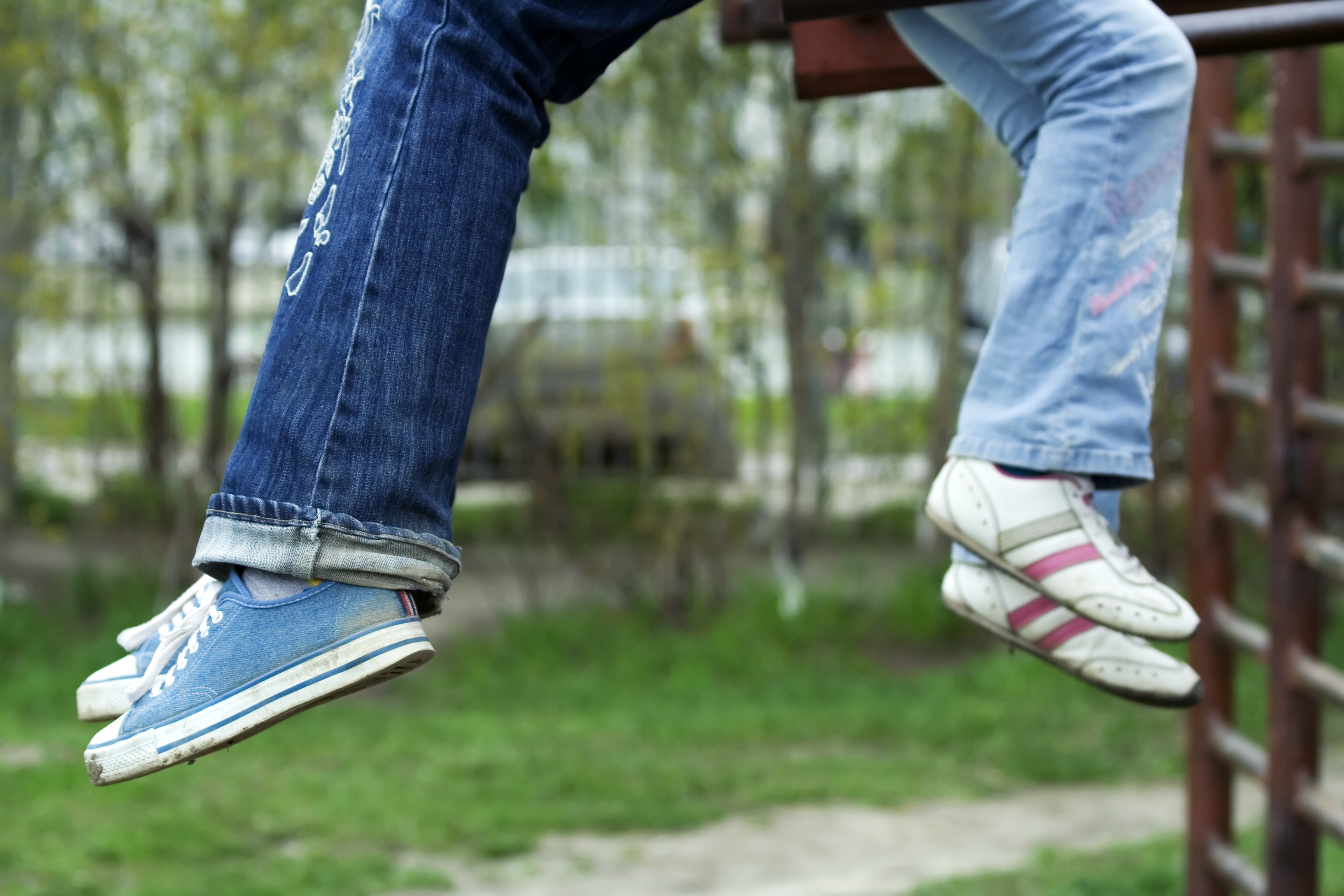 Legs of two young people wearing jeans and trainers.