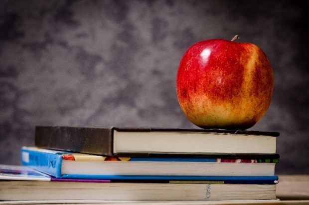 An apple balancing on a stack of books